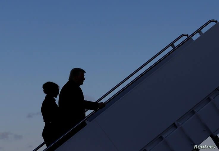 U.S. President Donald Trump departs next to first lady Melania Trump from the Joint Base Andrews, Maryland.