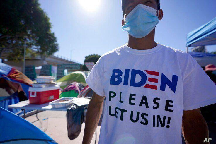 A Honduran man seeking asylum in the United States wears a shirt that reads,
