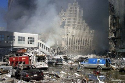 Fire trucks sit amid the rubble near the base of the destroyed World Trade Center in New York on September 11, 2001. Two hijacked commercial planes slammed into the twin towers of the World Trade Center Tuesday,