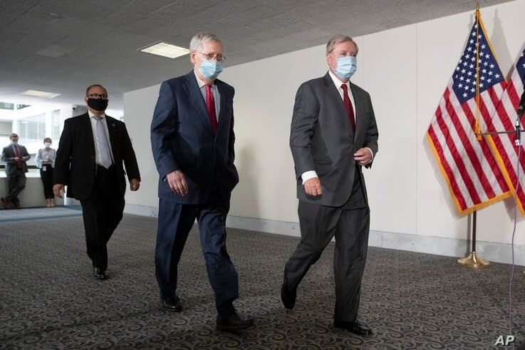 FILE - Senate Republican Majority Leader Mitch McConnell, left, and Republican Sen. Lindsey Graham, both wearing face masks to protect against the coronavirus walk on Capitol Hill, in Washington, May 19, 2020.