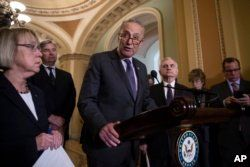 Senate Minority Leader Chuck Schumer, D-N.Y., joined by, from left, Sen. Patty Murray, D-Wash., Sen. Sheldon Whitehouse, D-R.I., and Sen. Jack Reed, D-R.I., responds to an announcement by Majority Leader Mitch McConnell that he intends to cancel the tradional August recess.