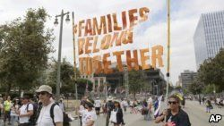 """FILE - Demonstrators hold signs as they participate in the """"Families Belong Together: Freedom for Immigrants"""" march, June 30, 2018, in Los Angeles."""