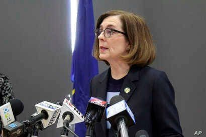 FILE - In this March 16, 2020, file photo, Oregon Gov. Kate Brown speaks at a news conference in Portland, Ore., to announce a…
