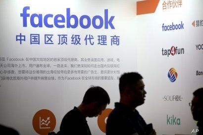 FILE - Visitors walk past the Facebook logo at an exhibitor's display at the Global Mobile Internet Conference (GMIC) in Beijing, April 26, 2018.