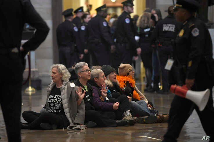 Protesters demonstrate against President Donald Trump by sitting on the floor of the Rotunda on Capitol Hill in Washington,…