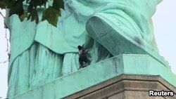 A protester is seen on the Statue of Liberty in New York, July 4, 2018, in this picture obtained from social media. (Danny Owens/via Reuters)