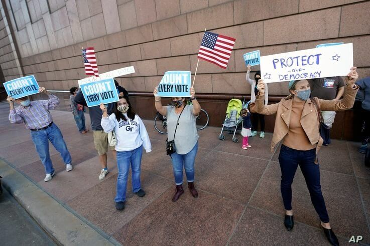Demonstrators stand across the street from the federal courthouse in Houston, Texas, Nov. 2, 2020, before a hearing in federal court involving drive-thru ballots cast in Harris County.