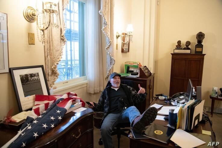 A supporter of US PreA supporter of President Donald Trump sits inside the office of Speaker of the House Nancy Pelosi inside the Capitol in Washington, Jan. 6, 2021. sident Donald Trump sits inside the office of US Speaker of the House Nancy Pelosi as he protest inside…