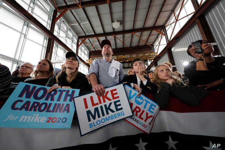 People listen as Democratic presidential candidate and former New York City Mayor Mike Bloomberg speaks at a campaign event in…