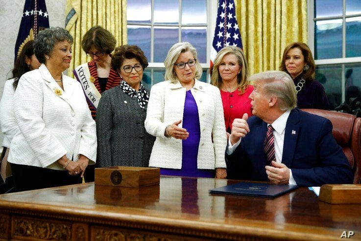 FILE - In this Nov. 25, 2019, file photo, Rep. Liz Cheney, R-Wyo., center, speaks with President Donald Trump during a bill…