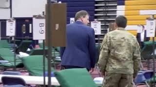 The Governor of New Hampshire visits a gymnasium retrofitted as an overflow hospital.