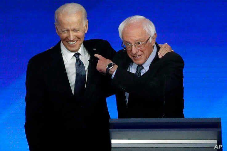 Former Vice President Joe Biden, left, embraces Sen. Bernie Sanders, I-Vt., during a Democratic presidential primary debate,…