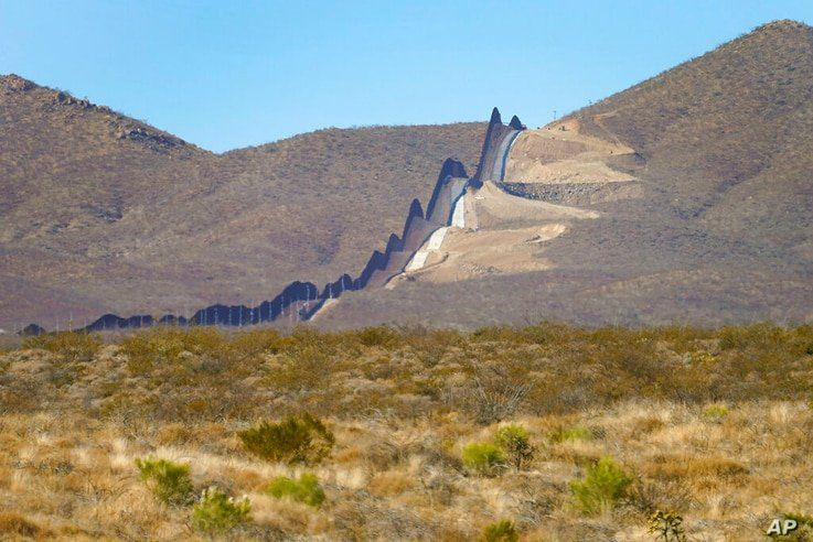 Newly erected border wall separating Mexico, left, and the United States, cuts through through the Sonoran Desert just west of…