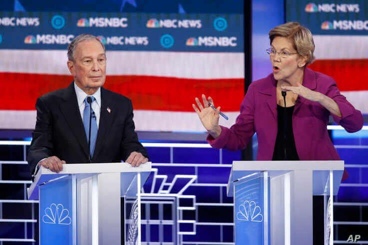 Democratic presidential candidates, former New York City Mayor Mike Bloomberg, left, listens as Sen. Elizabeth Warren, D-Mass.,…