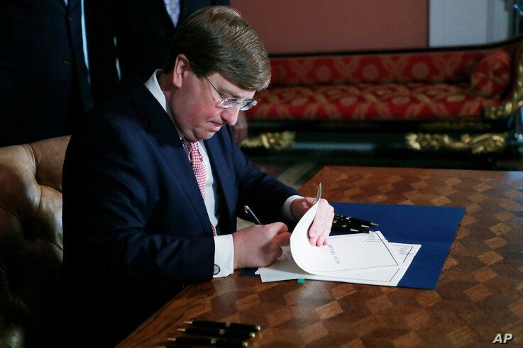 Mississippi Gov. Tate Reeves signs the bill retiring the last state flag in the United States with the Confederate battle…