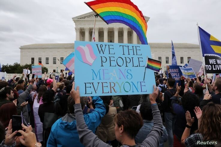FILE - LGBTQ activists and supporters hold a rally outside the U.S. Supreme Court as it hears arguments in a major LGBTQ rights case in Washington, Oct. 8, 2019.