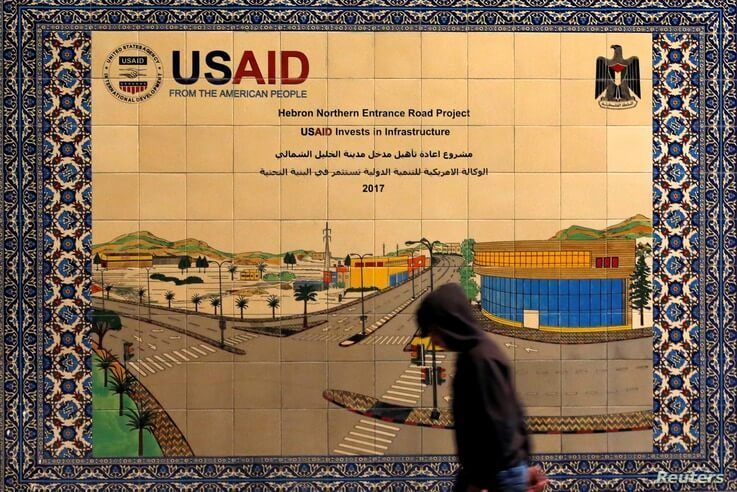 A Palestinian walks past a ceramic sign of a U.S. Agency for International Development (USAID) project in Hebron in the Israeli…
