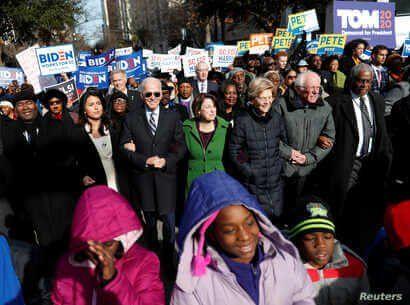 Democratic presidential rivals Tulsi Gabbard, Joe Biden, Amy Klobuchar, Elizabeth Warren and Bernie Sanders link arms during a Martin Luther King Jr. Day march, Jan. 20, 2020, in Columbia, South Carolina.