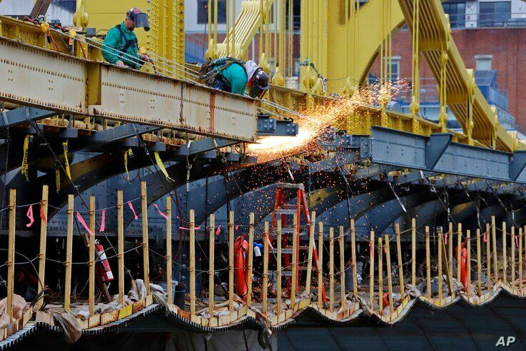 FILE - In this May 6, 2020, file photo a worker welds on the Ninth Street bridge in Pittsburgh. Looking beyond the $1.9…