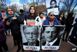 FILE - Amanda Bayer, left holding banner, and Marisol Maqueda, right with banner, from Mexico whose daughter Maria Torres also from Mexico City is a DACA recipient finishing her masters degree in Arizona, join a rally outside the White House in Washington