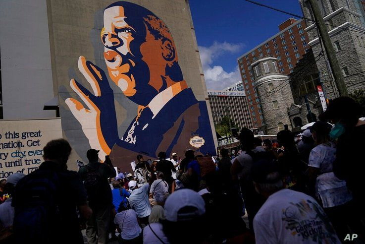 Demonstrators stop at the John Lewis Mural during a march for voting rights, marking the 58th anniversary of the March on…