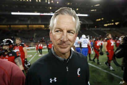 FILE - In this Nov. 18, 2016 file photo, Cincinnati coach Tommy Tuberville walks off the field after the team's NCAA college…