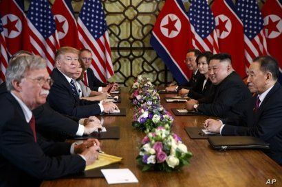 President Donald Trump speaks during a meeting with North Korean leader Kim Jong Un, in Hanoi, Vietnam, Feb. 28, 2019. At left is then-National Security Adviser John Bolton.