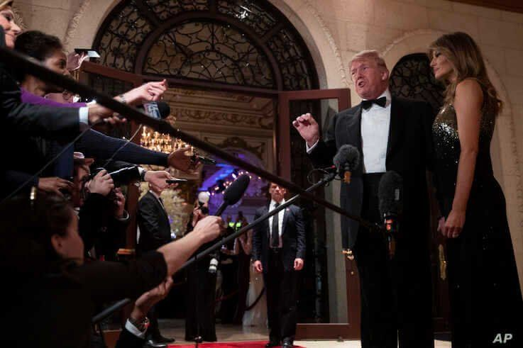 First lady Melania Trump listens as President Donald Trump speaks to reporters before his New Year's Eve party at his Mar-a…