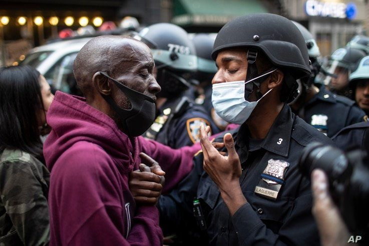FILE - A protester and a police officer shake hands in the middle of a standoff at a rally in New York City, June 2, 2020, calling for justice over the death of George Floyd.