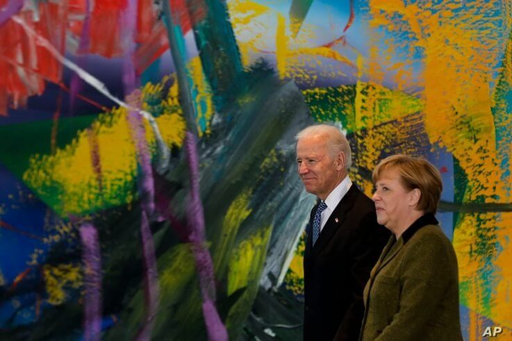 German Chancellor Angela Merkel, right, walks with United States' Vice President Joe Biden for a meeting at the chancellery in…