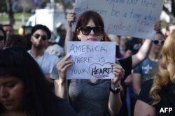 """Critics of U.S. government policy which separates children their parents when they cross the border illegally from Mexico protest during a """"Families Belong Together March,"""" in downtown Los Angeles, California, June 14, 2018."""
