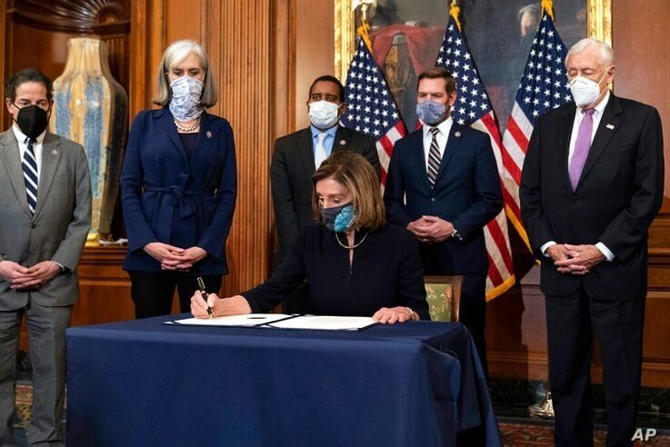 House Speaker Nancy Pelosi of Calif., signs the article of impeachment against President Donald Trump in an engrossment…