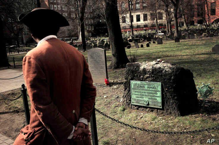 Samuel Ike, of Cambridge, Mass., left, dressed in the role of Revolutionary War-era African American abolitionist Prince Hall, walks past the grave with red flowers of the victims of the 1770 Boston Massacre, March 3, 2020.