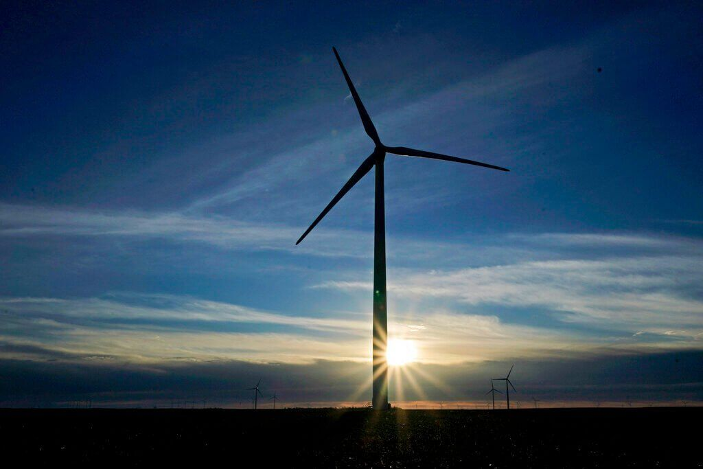 FILE - In this Jan. 13, 2021, file photo a wind turbine is silhouetted against the rising sun Wednesday, Jan. 13, 2021, near…
