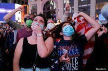 People react as they watch a speech by Democratic 2020 U.S. presidential nominee Joe Biden.