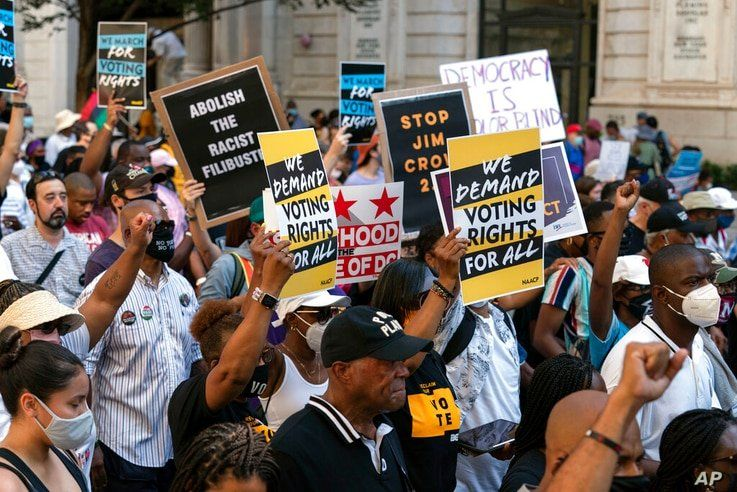 Demonstrators hold signs during a march for voting rights, marking the 58th anniversary of the March on Washington, Saturday,…
