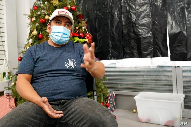 Gustavo Ajche, 38, who has three jobs, gestures after watching Joe Biden's presidential inauguration on TV with other…