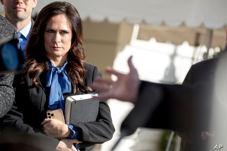 FILE - White House Press Secretary Stephanie Grisham listens as President Donald Trump speaks to reporters on the South Lawn of the White House in Washington, Nov. 8, 2019.