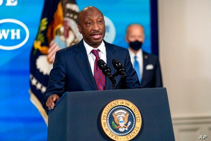 Merck Chairman and CEO Kenneth Frazier, left, accompanied by President Joe Biden, right, speaks in the South Court Auditorium…