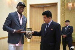 """FILE - Former NBA basketball star Dennis Rodman presents a copy of """"Trump: The Art of the Deal"""" to North Korean Sports Minister Kim Il Guk, June 15, 2017, in Pyongyang, North Korea."""