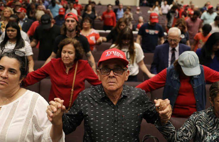 MIAMI, FLORIDA - JANUARY 03: People pray together during the 'Evangelicals for Trump' campaign event held at the King Jesus…