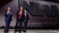 FILE - NRA Executive Director Chris Cox, left, and Executive Vice President and CEO Wayne LaPierre, right, welcome U.S. President Donald Trump onstage to deliver remarks at the National Rifle Association (NRA) Leadership Forum.