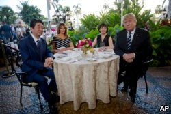 FILE - President Donald Trump and first lady Melania Trump sit with Japanese Prime Minister Shinzo Abe and his wife, Akie Abe, for dinner at Trump's private Mar-a-Lago club, April 17, 2018, in Palm Beach, Fla.