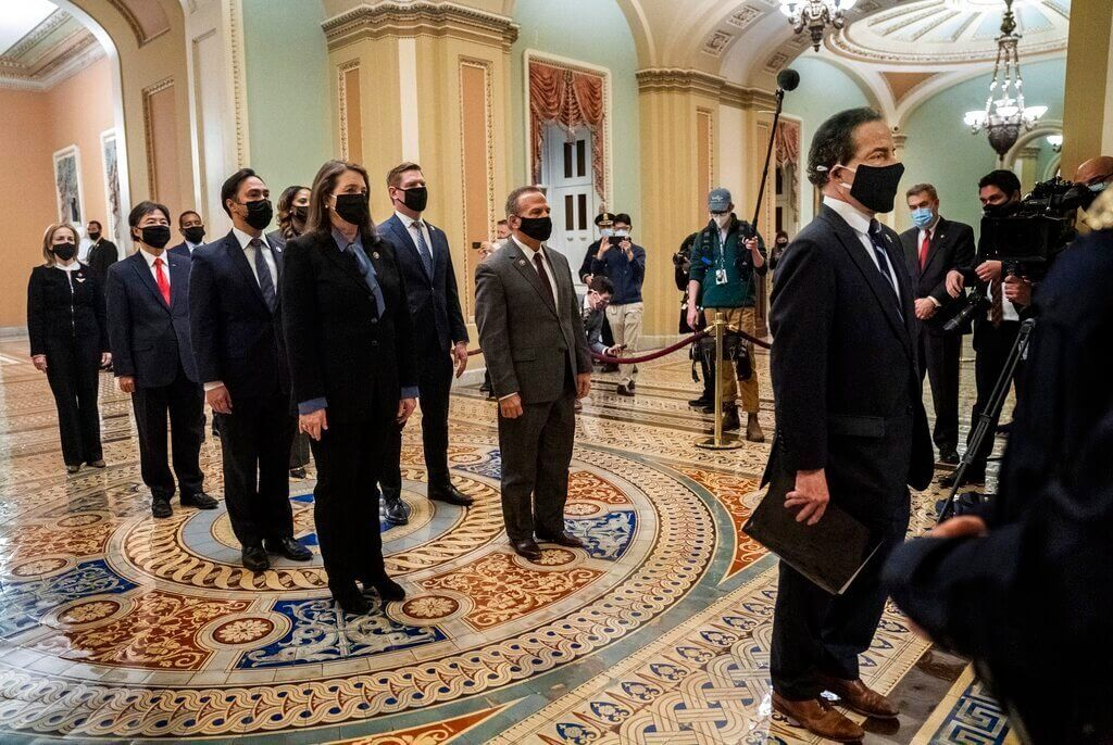 Democratic House impeachment managers stand before entering the Senate Chamber as they deliver to the Senate the article of…
