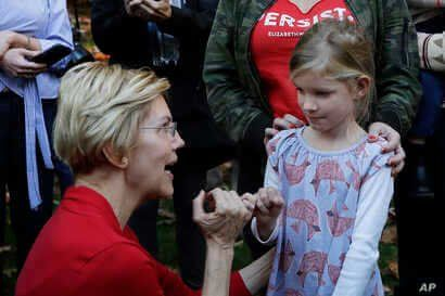 Democratic presidential candidate Sen. Elizabeth Warren, D-Mass., makes her signature pinky promise with Nora Showalter, 6, at…