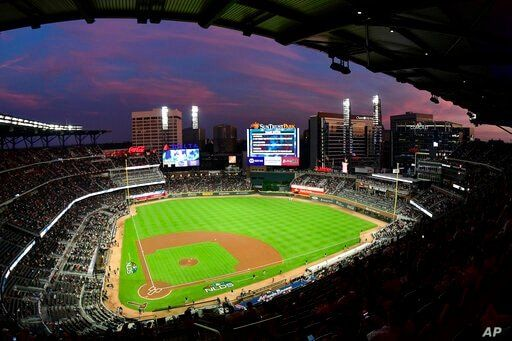 FILE - In this Oct. 7, 2018, file photo, ground crews prepare the field at Sun Trust Park, now known as Truist Park, ahead of…