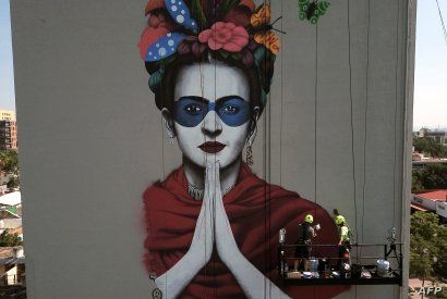 Irish urban artist Fin Dac (2-R) and his assistant work on his mural