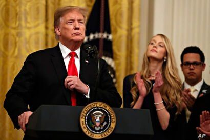 President Donald Trump adjusts his blazer as he speaks before signing an executive order requiring colleges to certify that their policies support free speech as a condition of receiving federal research grants, March 21, 2019, in the East Room of the White House in Washington.