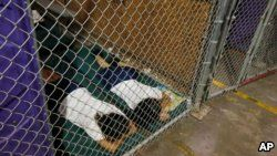 FILE - Two female detainees sleep in a holding cell, as the children are separated by age group and gender, as hundreds of mostly Central American immigrant children are being processed and held at the U.S. Customs and Border Protection Nogales Placement Center in Nogales, Arizona, June 18, 2014.