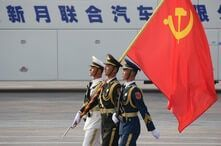 Soldiers of People's Liberation Army (PLA) march in formation with a Chinese Communist Party flag during a rehearsal before…